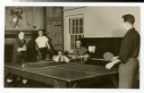 Male students playing and watching ping pong in the recreation room of the male dorm