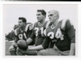 Three football players kneeling for photo in 1964.