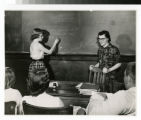 Female student writing on chalkboard with smiling teacher looking at class