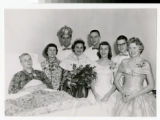 Homecoming king and queen with group at the side of a student's bed 1957-58