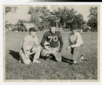 Bethel football team captain and coaches kneeling on field