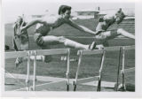 Men's track athletes jumping over hurdles