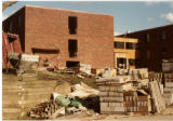 Exterior shot of Getsch Hall under construction, materials in foreground