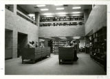 View of first floor library, students at card catalogs