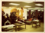 First floor library interior, two students studying in front of mural wall