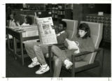 Students in first floor library reading (news)papers