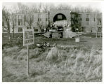 Frontal shot of Nelson Hall under construction, Bethel College Location sign in foreground