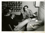 Two males (both students?) talking in dorm room