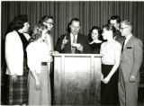 Debate, seven students crowded around podium