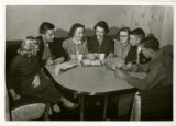 Group of students around table with cups, Bibles