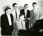 Five male students around piano, one with saxophone