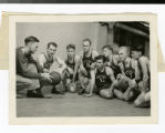 Basketball team kneeling on floor in gymnasium listening to coach