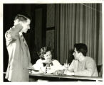 Three students, two sipping at soda counter (theater production of Our Town)