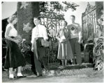 Four students, two standing in front of wrought iron gate