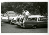 Three male students standing on back of car