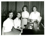 "Four female students at piano, candidates for """"Freshman Sweetheart"""" title"